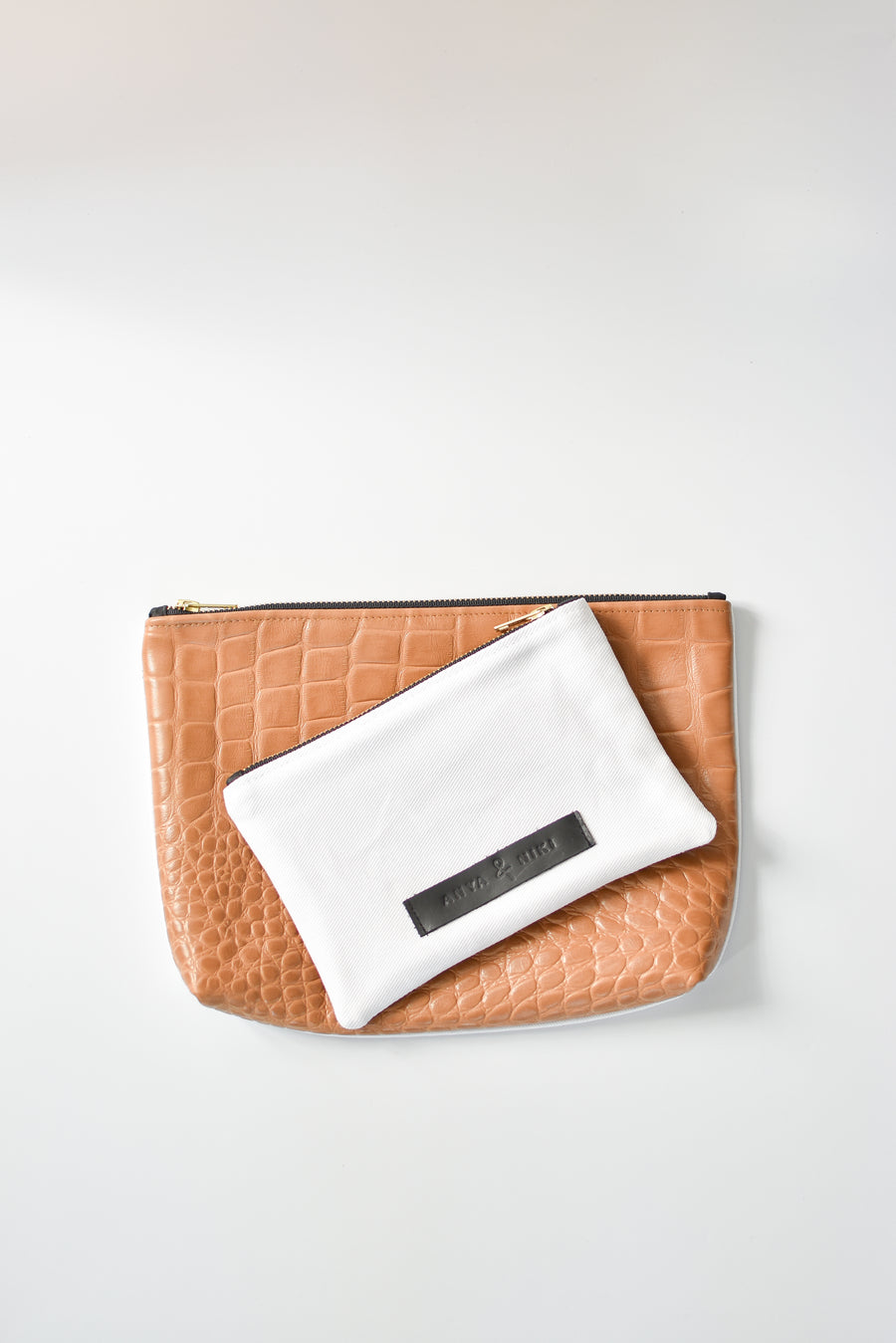 White denim and caramel colored embossed leather skin small and medium pouch with brass zipper and leather logo label.