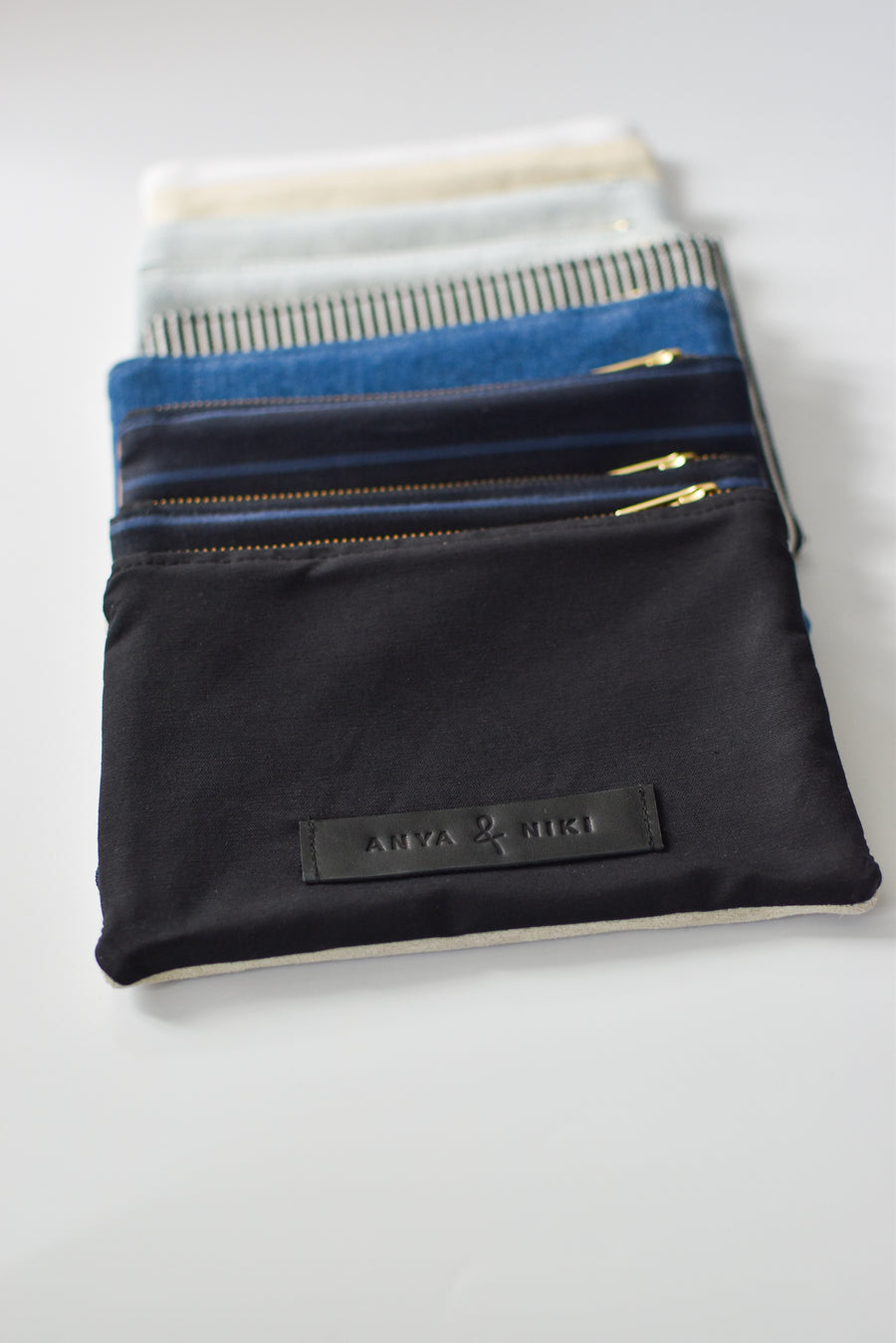 Collection of small limited edition leather and denim pouches from Anya & Niki.