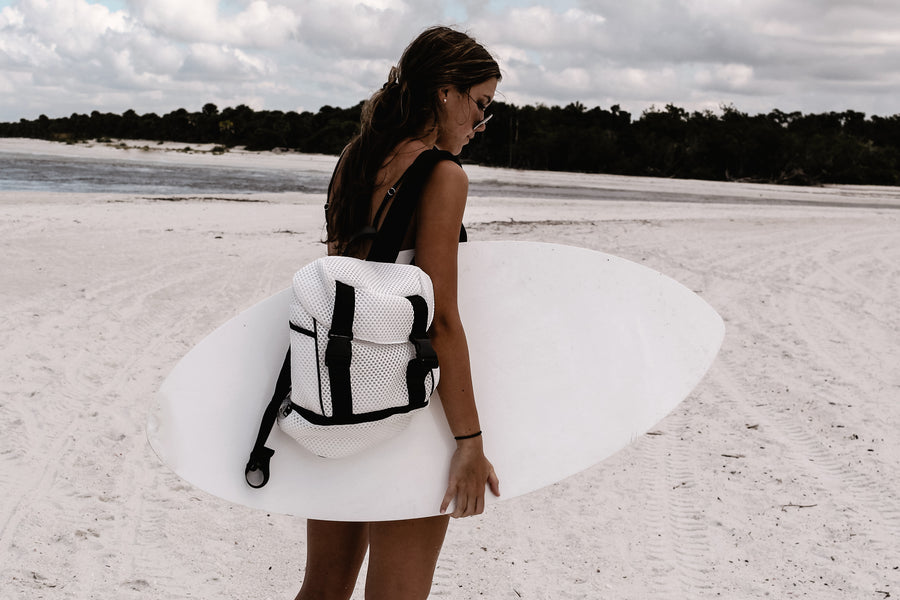 Brooker white mesh backpack with black trim details on model at beach with surf board.