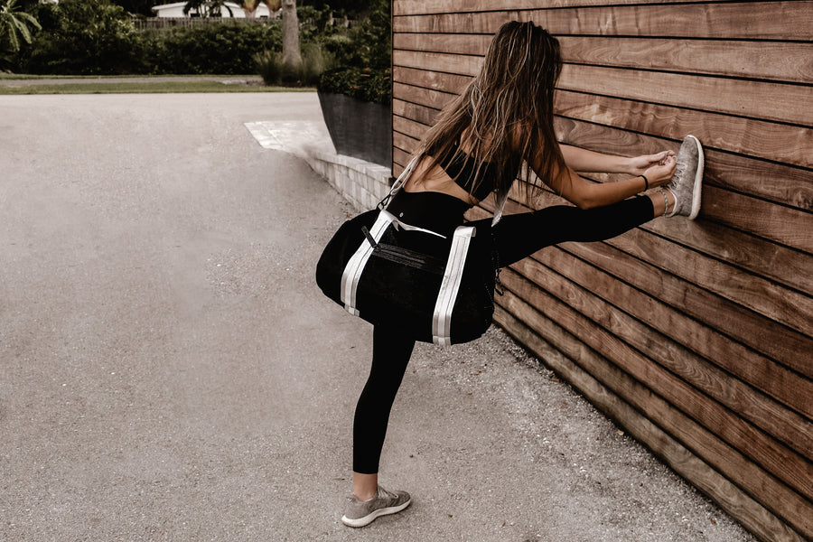 Model wearing black velour duffel bag with white straps and leather details, while stretching on wood wall.