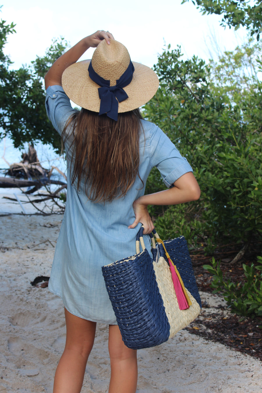 Natural raffia straw panama hat with navy grosgrain tie on model holding navy and natural straw bag with circle hand and suede tassel.
