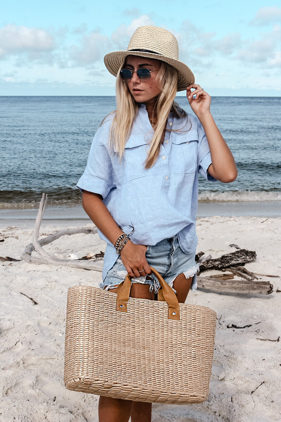 person at beach, holding large straw tote bag finished with natural leather handles and wearing straw fedora hat.