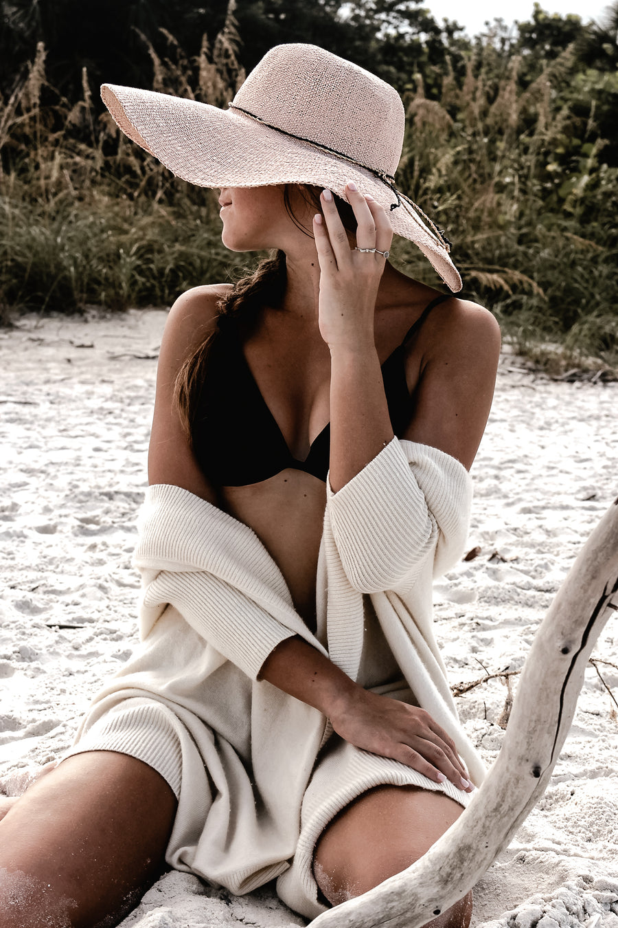 Pink floppy straw hat with raffia braid on model at beach.