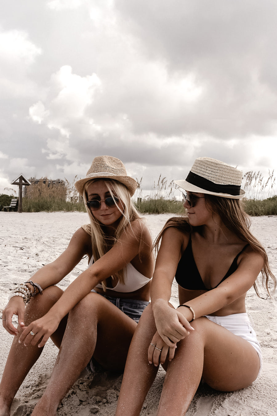 Models at beach wearing crochet straw fedora hat with rope band and classic straw fedora hat with black grosgrain band.