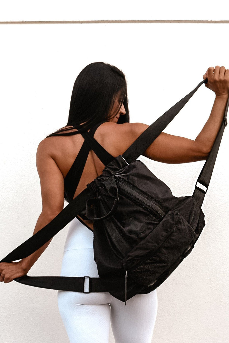 Black nylon convertible backpack tote with leather details on model.