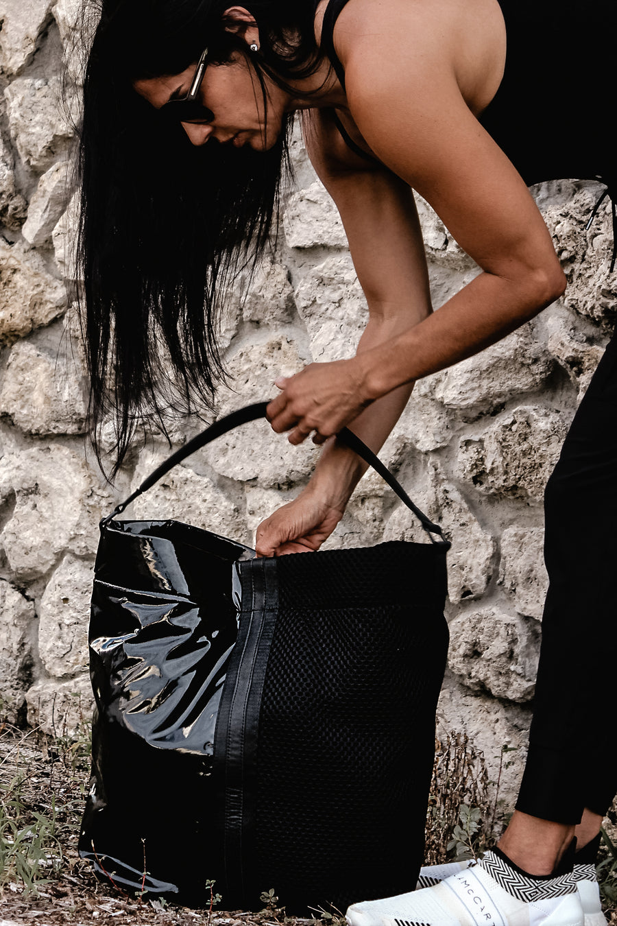 Model with black mesh and glossy vinyl sporty tote bag with black leather and webbing details.