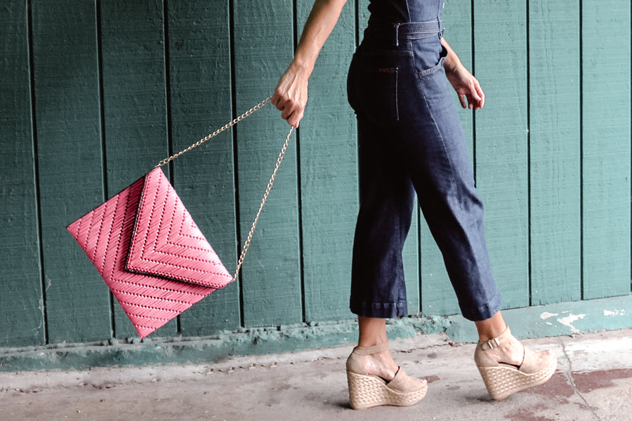 Model holding bright pink woven raffia straw clutch by detachable gold chain strap.