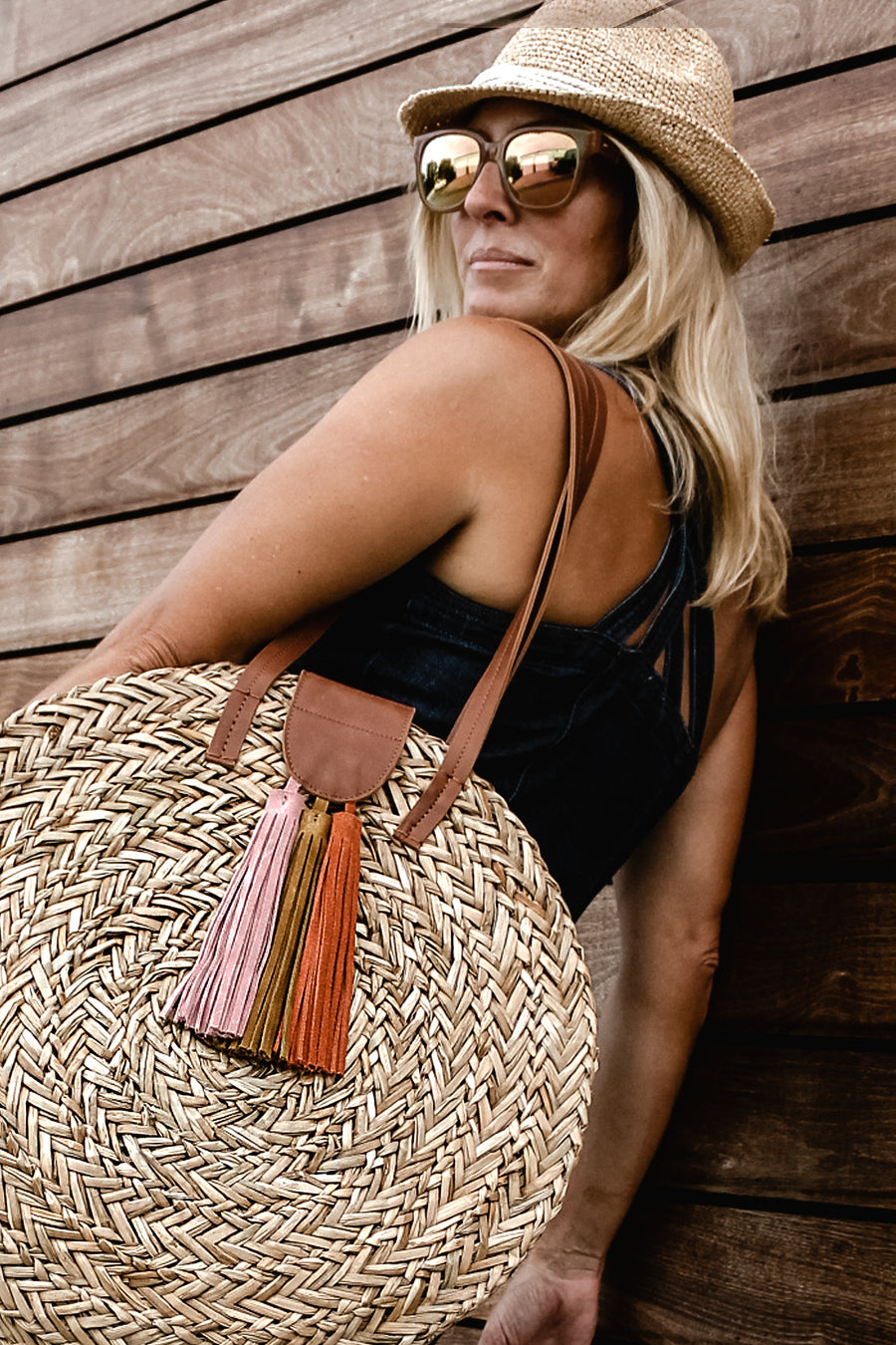 person wearing seagrass round straw bag with leather handles and suede tassel closure and crochet straw fedora.