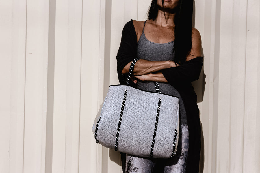 Person holding the Anya & Niki gray neoprene tote bag with shiny silver adjustable sides and cord handles.