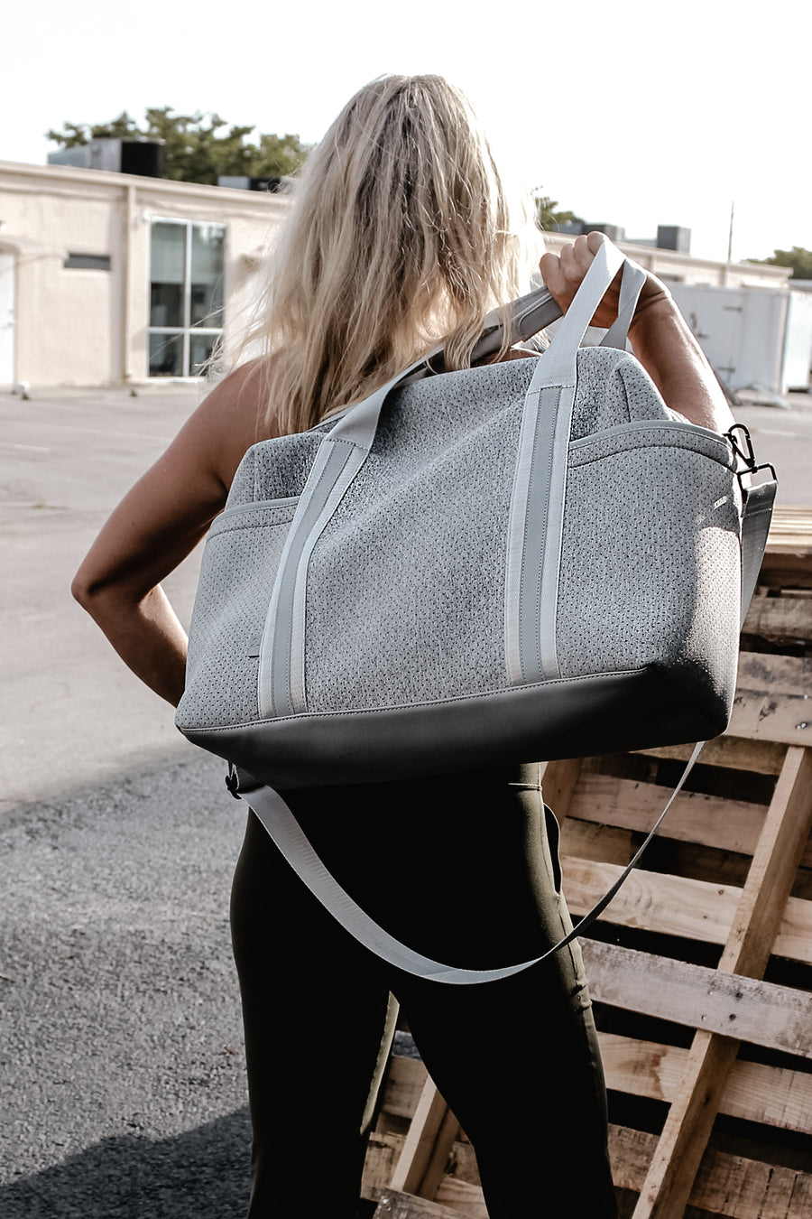 Callahan light gray perforated neoprene duffel bag on model.