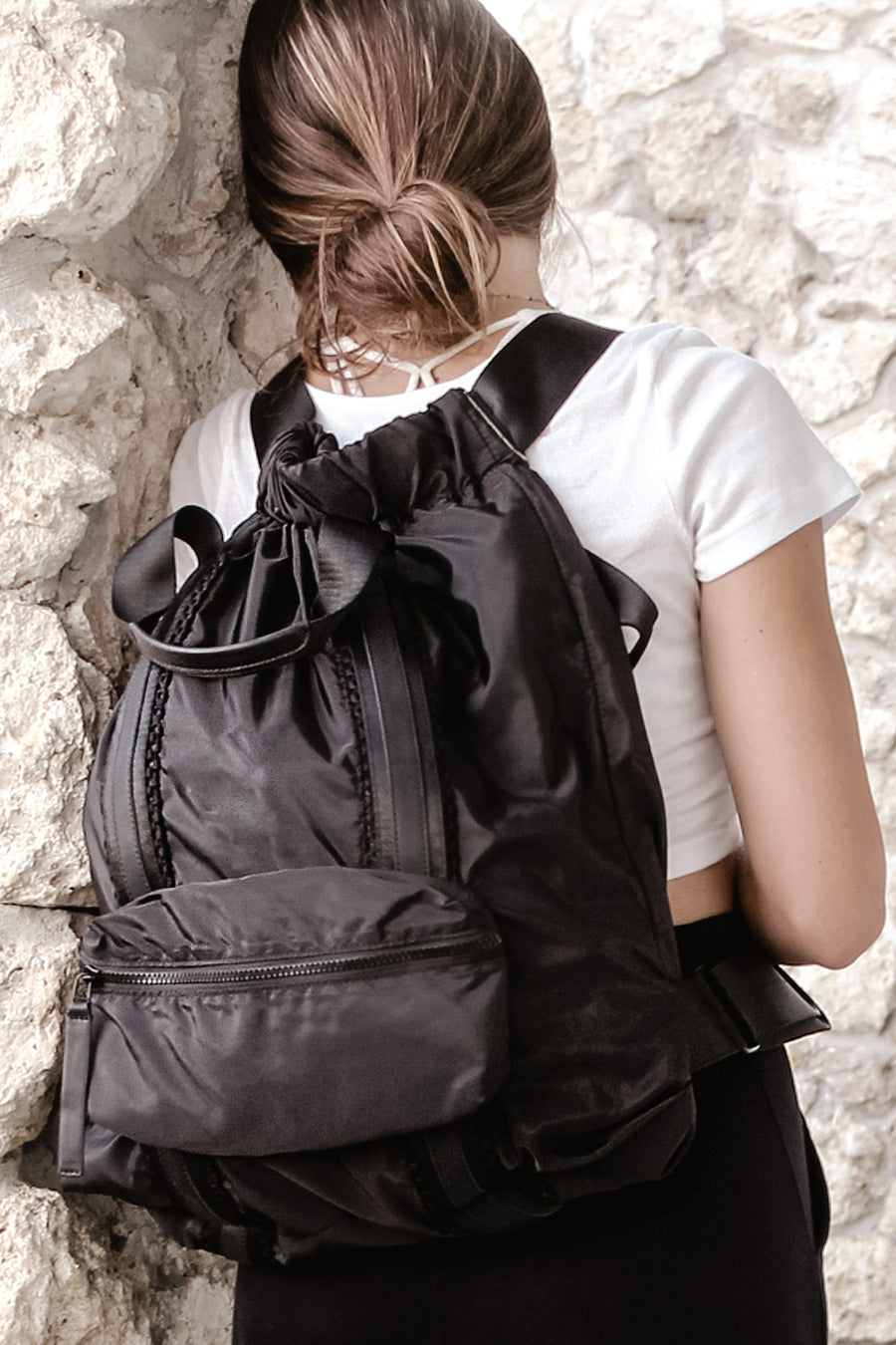 Black nylon convertible backpack tote with leather details shown on model.