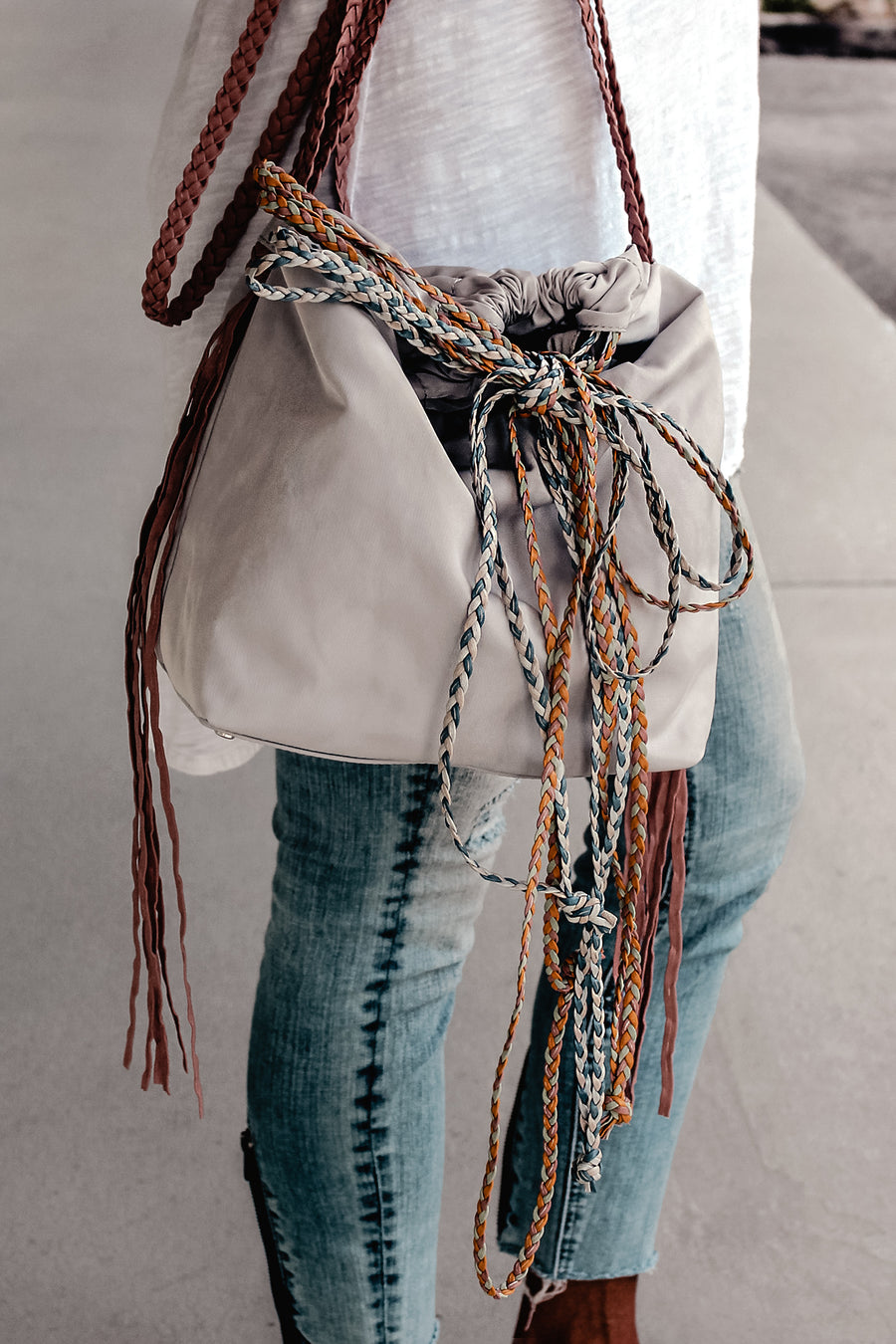 person wearing sporty gray nylon cinch bag with colorful braided leather straps.