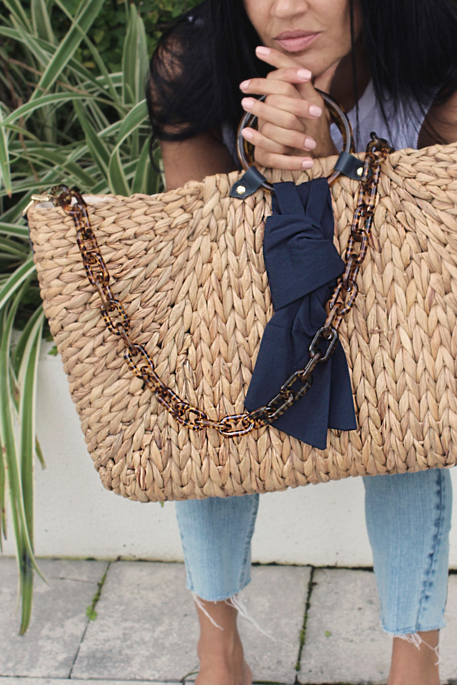 person holding extra-large hyacinth straw tote with torte and navy accents.