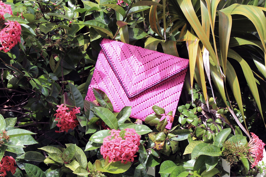 Bright pink woven raffia straw clutch nestled into flowers and foliage.