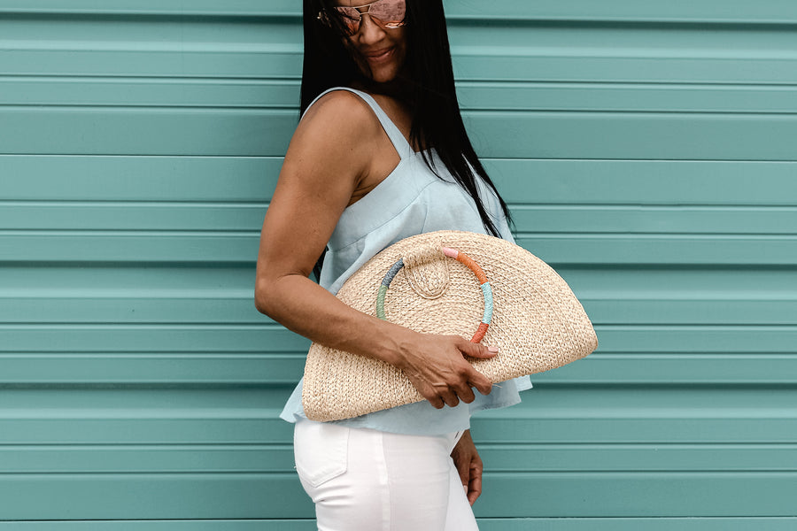 Model holding natural raffia straw half-moon clutch with rainbow colored wrapped circle handle and leather sides.