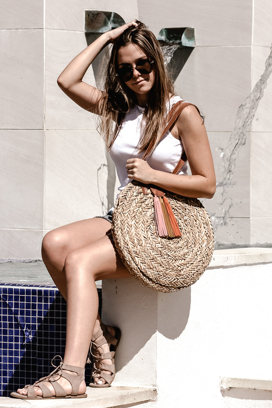 person holding natural seagrass round straw bag with leather handles and suede tassel closure.