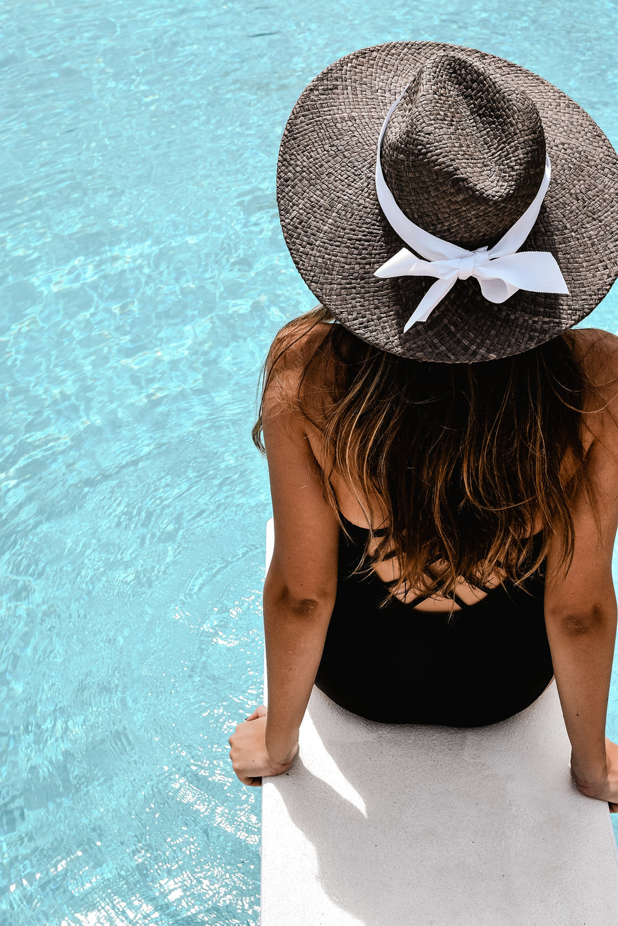Gray raffia straw panama hat with white grosgrain tie on model sitting on pool diving board.