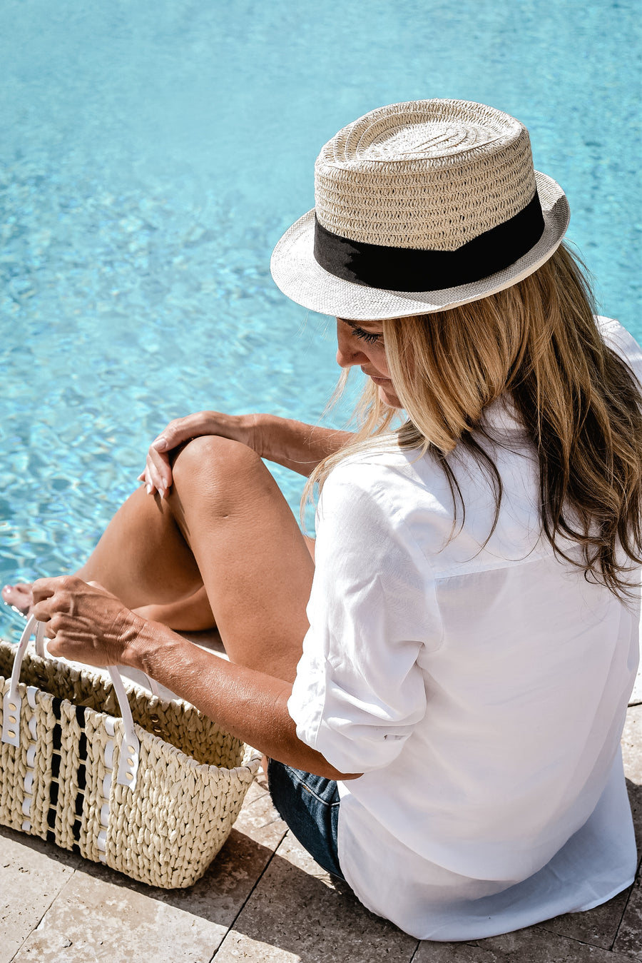 Model sitting by pool, wearing fedora hat with black grosgrain band and holding small straw tote with white leather handles.