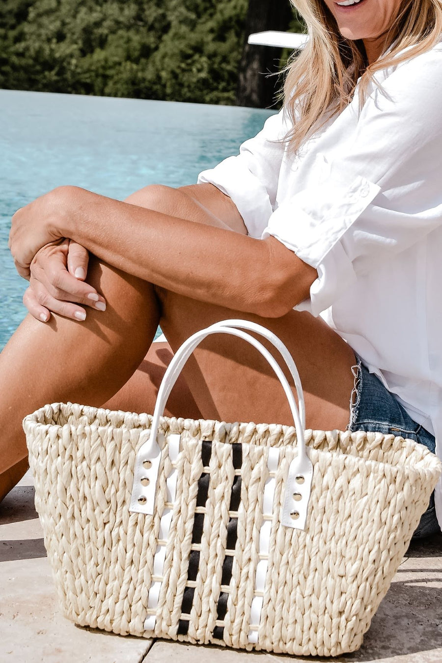 Person sitting by pool with small woven straw tote bag laced with black and white leather.