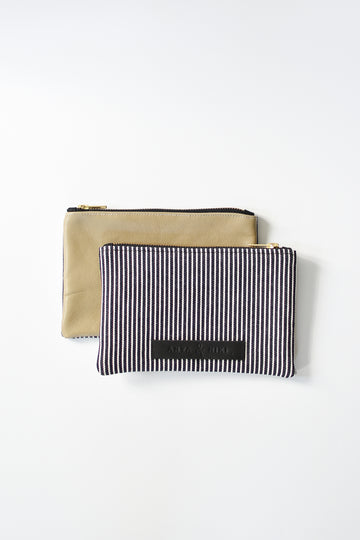 Railroad striped denim and taupe colored leather small pouch with brass zipper and leather logo label.