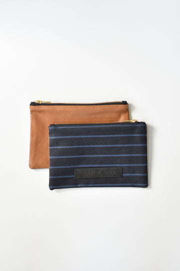 Striped dark denim and brown leather small pouch with brass zipper and leather logo label.