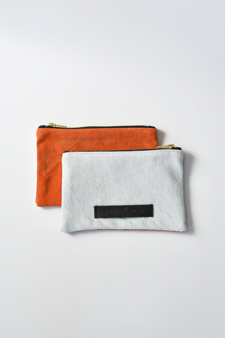 Washed denim and orange suede small pouch with brass zipper and leather logo label.