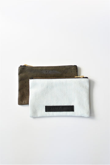 Bleached denim and fern colored embossed leather skin small pouch with brass zipper and leather logo label.