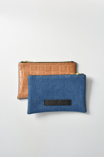 Medium wash denim and caramel colored embossed leather skin small pouch with brass zipper and leather logo label.