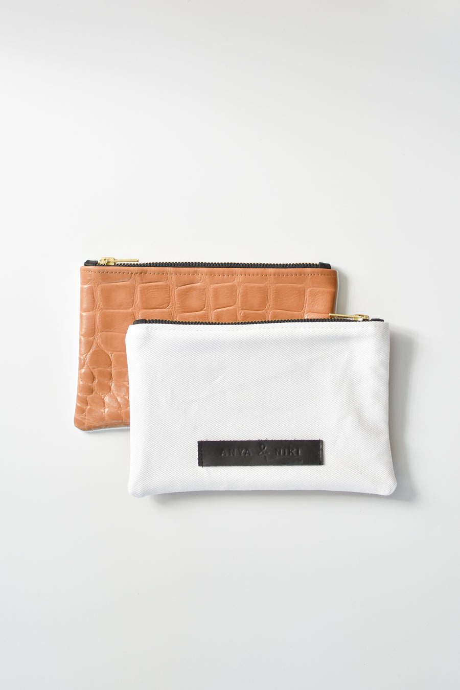 White denim and caramel colored embossed leather skin small pouch with brass zipper and leather logo label.