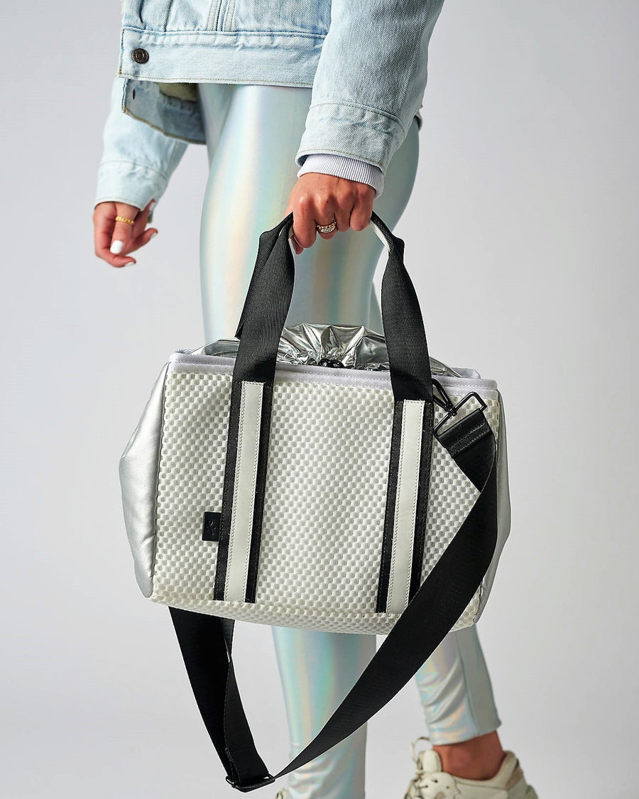 Person holding the Anya & Niki small white mesh tote with silver cinch top and crossbody strap