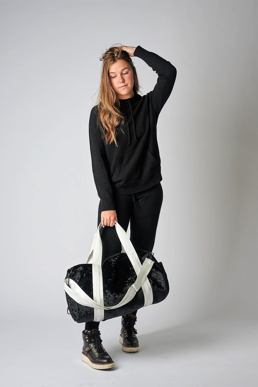 person holding black velour duffel bag with white straps and leather details