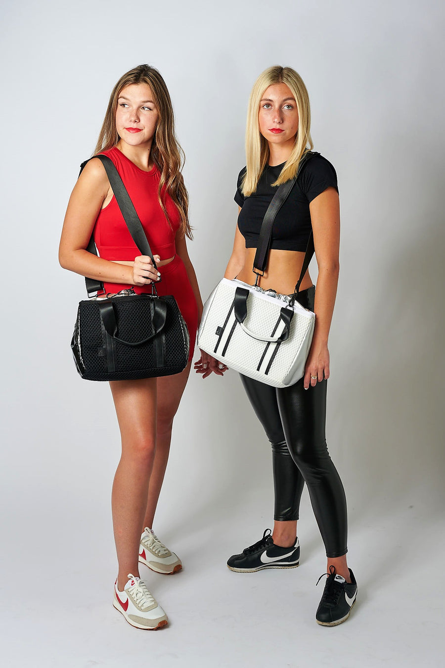 two people wearing black and white mesh crossbody totes