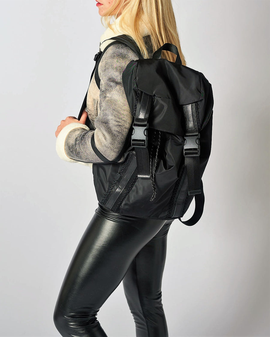 Person wearing the Delray black nylon backpack with mesh back and leather details.
