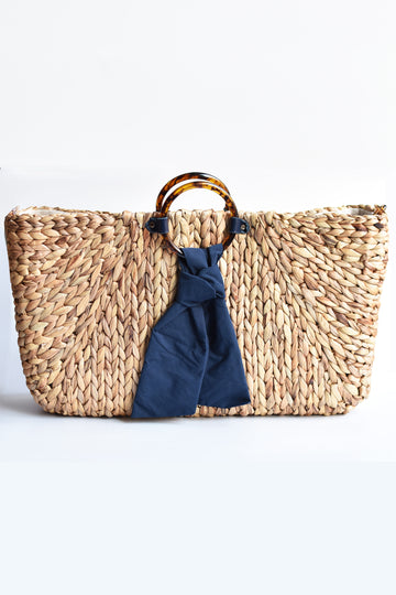 Extra-large hyacinth straw tote with faux torte circle handle and navy tie front.