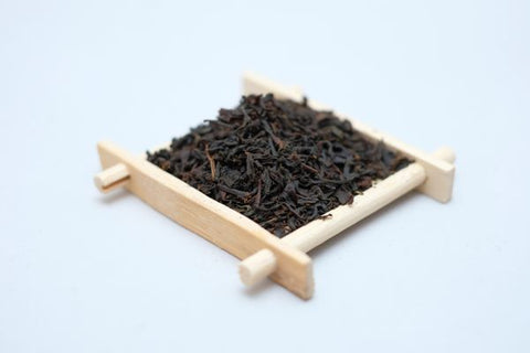 A picture of a bamboo coaster full of Earl Grey Tea leaves from Red Moon Tea.