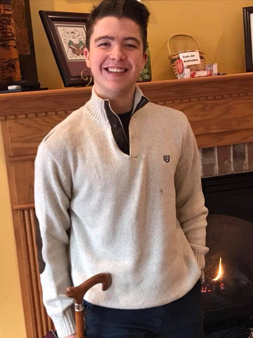 Mitchell Herndon, standing and smiling in front of a fireplace.