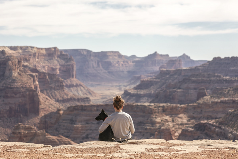 Woman sits on cliff overlooking canyons with an arm around his adopted dog.