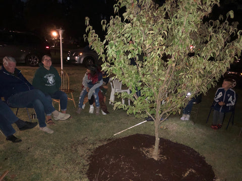 Family gathered around tree memorial, planted with human cremains mixed with Let Your Love Grow.