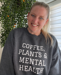"""Allison is the co-owner of Own Your Stigma. She is wearing a grey crewneck sweatshirt with the words """"Coffee, Plants & Mental Health"""" written on it."""