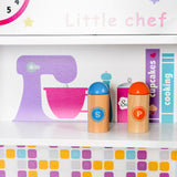The toy kitchen includes a shelf for storing cook books and more