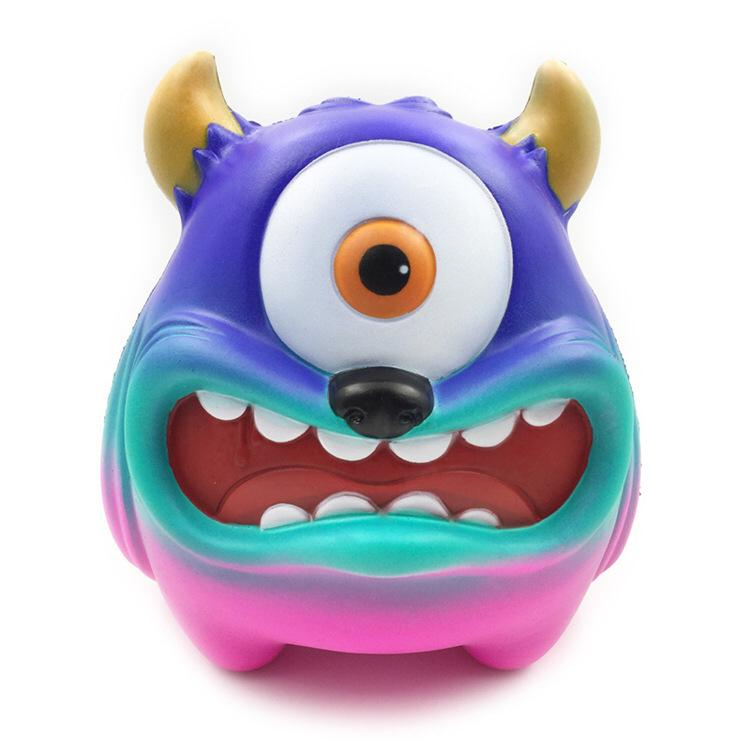 A gradient coloured monster featuring blue, mint and pink colours. Has one big white and round eye, black nose and an open mouth showing its teeth and two golden horns as ears.