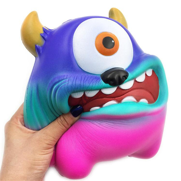 A hand squishing a gradient coloured monster featuring blue, mint and pink colours. Has one big white and round eye, black nose and an open mouth showing its teeth and two golden horns as ears.
