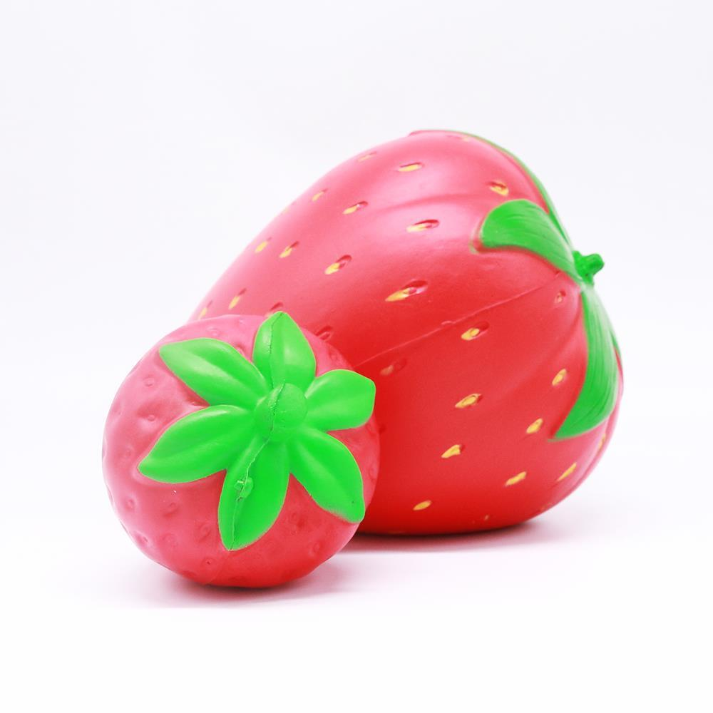 Two red strawberry squishies laying on their sides with green leaves on top. One is bigger than the other