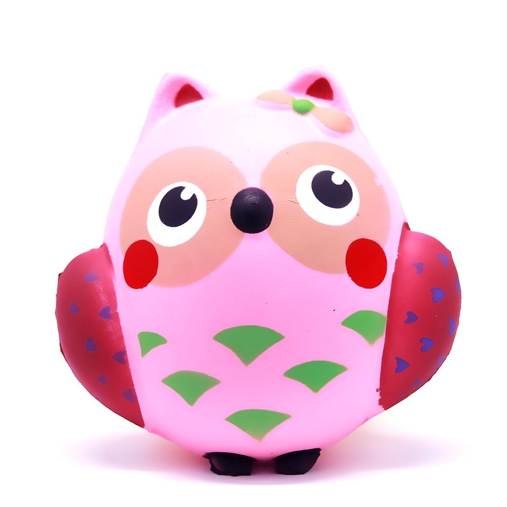 A pink squishy in the shape of an owl with big round eyes,  pink belly with green spots, red wings with purple hearts and a pink bow on its left ear