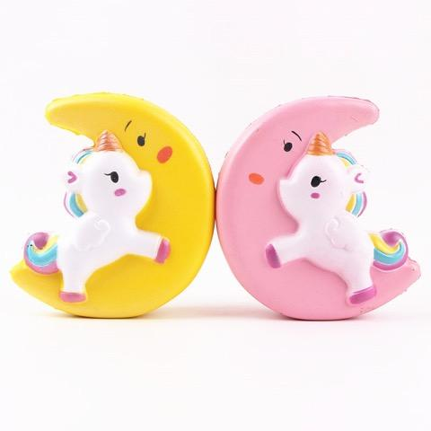 Two squishies. A white unicorn on a yellow half moon and a white unicorn on a pink half moon.