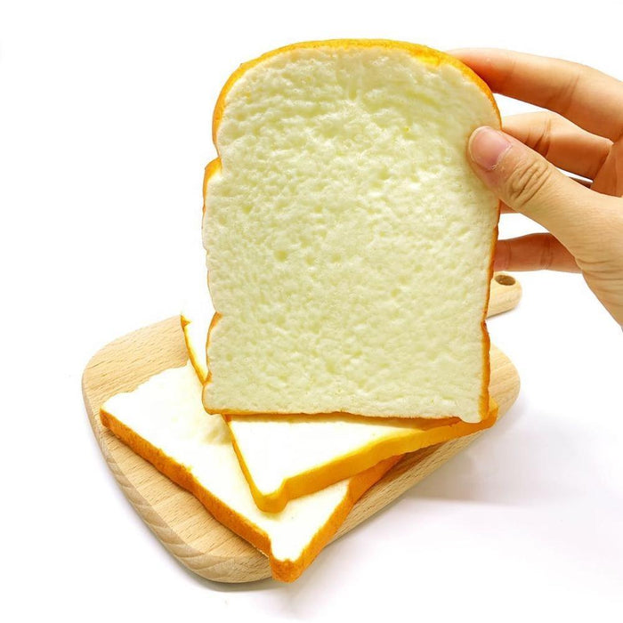 A hand holding a squishy that looks like a slice of white bread