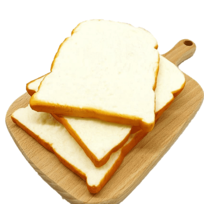 Three squishies that look like slices of white bread on a wooden table