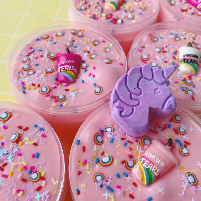 Pink slime with rainbow sprinkles, star sprinkles, confetti sprinkles, a unicorn tears charm and purple air-dry clay unicorn.