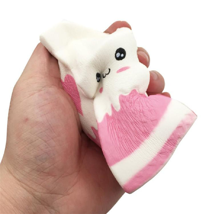A hand squishing a white and pink milk carton squishy