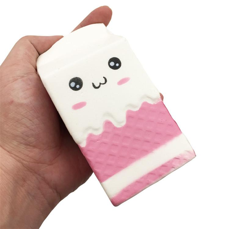 A hand holding a white and pink milk carton with round black eyes and pink cheeks